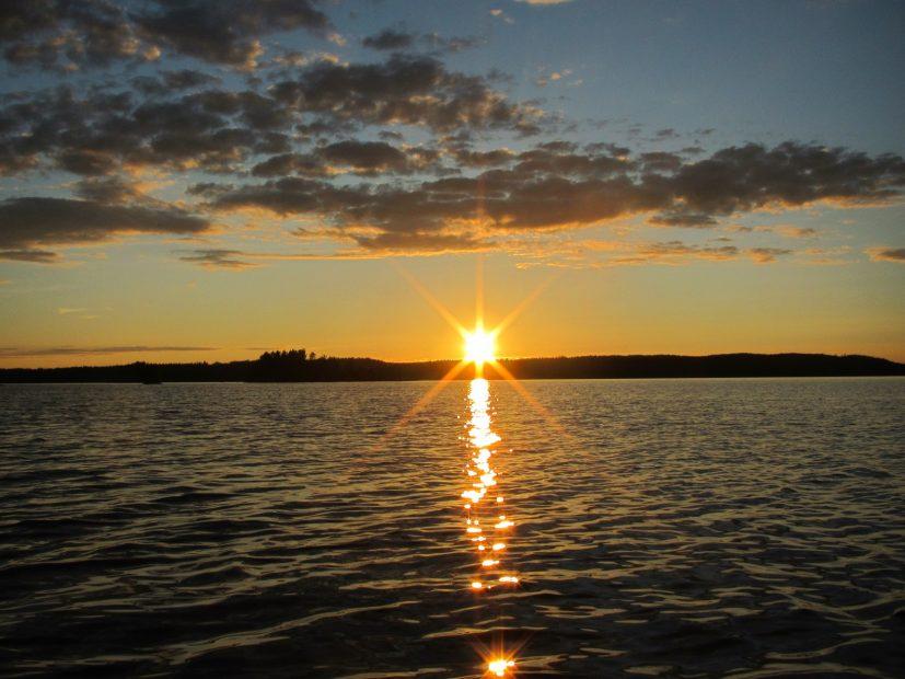 Die Sonne geht unter über einem finnischen See