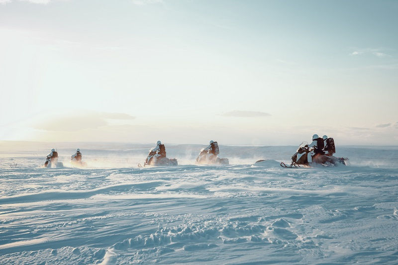 Darsteller auf Schneemobilen in Arctic Circle
